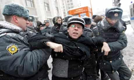 Russian police officers detain a protester outside the Duma