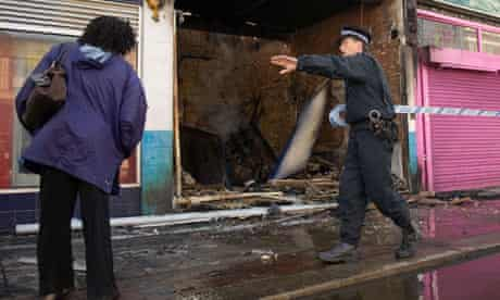 Police officer sets up a cordon around a burnt-out shop
