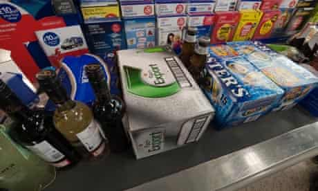 Cartons of beer and bottles of wines and spirits on a supermarket checkout belt