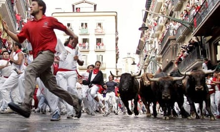 Men being chased by bulls on the streets of Pamplona