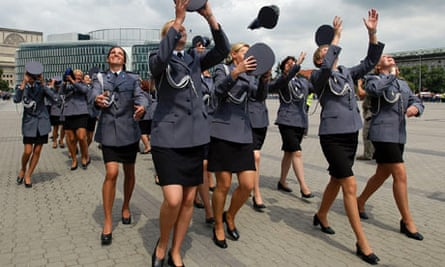 Female police officers throw their caps into the air