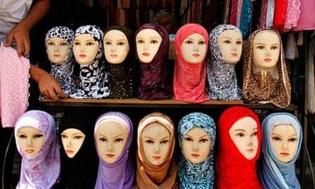 Jordanian vendor arranges headscarves for sale, in downtown Amman