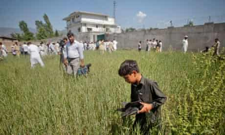 A boy collects debris as journalists surround the compound where Osama bin Laden died
