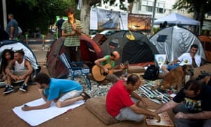 Protesters sit outside their tents in Tel Aviv