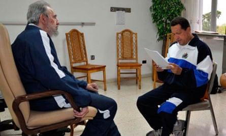 Fidel Castro looks on as Hugo Chavez reads a document