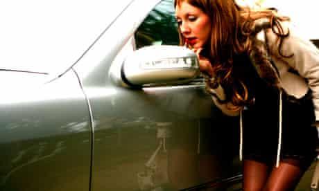 A prostitute applying lipstick