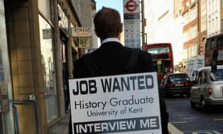 A university graduate wears a sandwich board advertising himself as he seeks employment