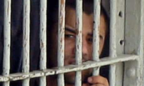 Iraqi prisoner looks through cell bars