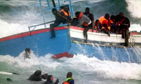 Rescuers help Libyan migrants who fled to the Italian island of Pantelleria i