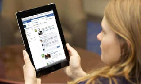 Young woman checking her Facebook page on an iPad2