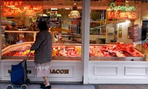A woman looks through the window of a butchers shop