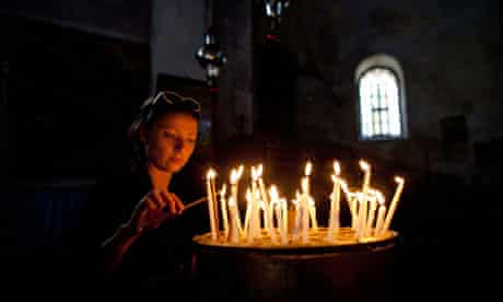 A woman lights candles in the Church of the Nativity, Bethlehem.