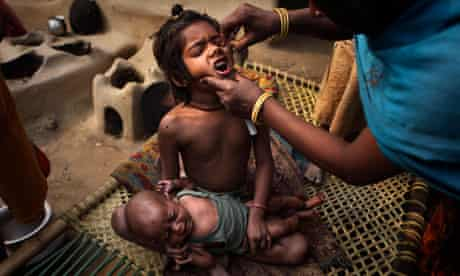 A health worker gives polio drops to a child in a village near Patna, India