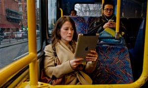 Young women reading novels on both a Kindle and an iPad on public transport