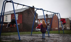 children by swings in rain on housing estate