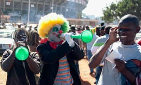 Zimbabweans football fans play the vuvuz