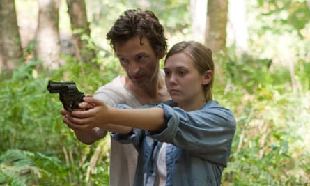 Martha Marcy May Marlene film still showing two people in the woods with a gun