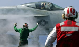The pilot of a F/A-18 Hornet jet fighter prepares to take off from a US aircraft carrier.