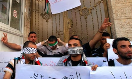 Palestinian men sit outside HQ of the International Committee of the Red Cross (ICRC) in Gaza