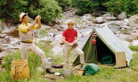 A man and a teenage boy camping next to a river