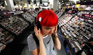 A girl at a listening post inside a record shop