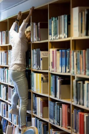 A dancer hangs off the book shelves in Cern's library