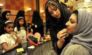 A Saudi woman applies makeup on a woman