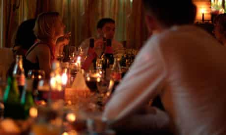 People Sitting Around a Candlelit Dining Table Enjoying Food and Drink