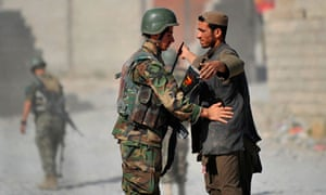 A soldier of the Afghanistan National Army checks a villager during a patrol in Helmand Province
