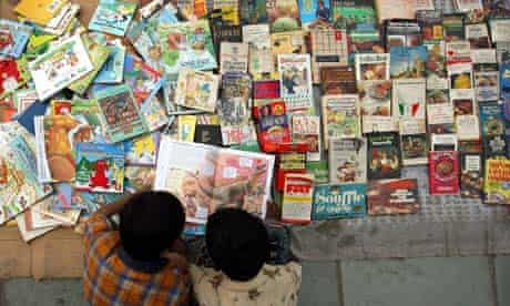 Boys browse a book at a roadside shop in the old quarter of Delhi