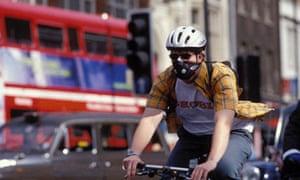 Cyclist in morning rush hour wearing smog mask helmet Islington London UK