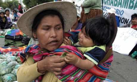 Bolivian woman gives her baby coca leaves