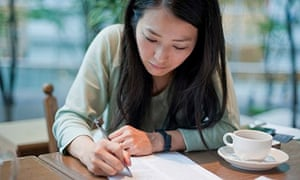 Mid adult woman writing on paper in cafe