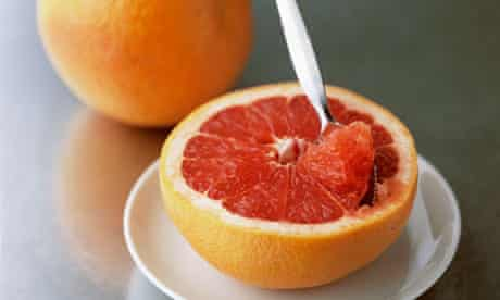 Half grapefruit with spoon and whole grapefruit