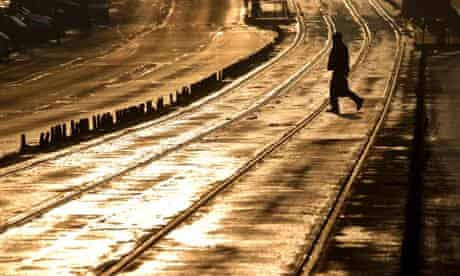 A man is silhouetted by the setting sun while crossing tram lines in Bucharest, Romania