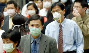 People wear masks on the streets of Hong Kong following the outbreak of Sars, March 2003.