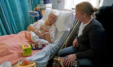 Daughter visiting elderly mother patient in hospital