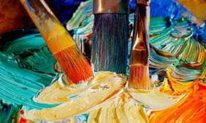 High angle view of paintbrushes mixing paint on a palette