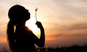 Silhouette of a young girl blowing dandelion seed head at sunset
