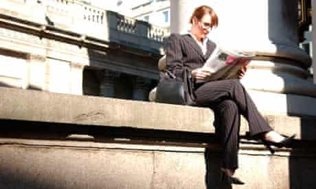 British businesswoman reading newspaper in the City of London