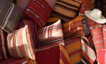 Cushions and rugs piled in souk , Marrakesh , Morocco , North Africa