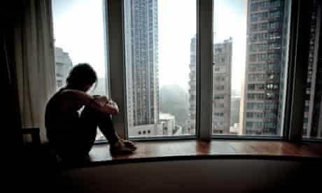 Lonely girl looking out of apartment window