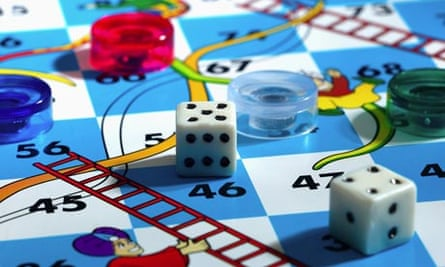 Close up of a snakes and ladders board with dices and tokens