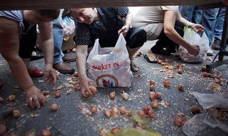 People crouch to collect leftover vegetables in Athens