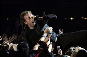 Chris Martin of Coldplay singing while stage diving