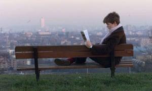 A woman reading a self-help book on Hampstead Heath