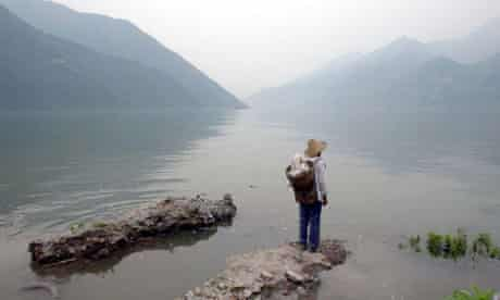 Han Xianzhong, a 70-year-old man, stands at the site of his dismantled house in the Three Gorges area, June 2003