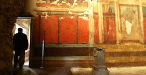 A visitor stands inside a room at the House of Augustus on the Palatine hill in Rome