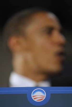 An Obama logo is seen in the foreground as the Democratic presidential candidate, Sen. Barack Obama, D-Ill., speaks during a town hall-style meeting in Powder Springs, Ga., Tuesday, July 8, 2008