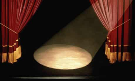 A Stage With A Spotlight And Drawn Curtains